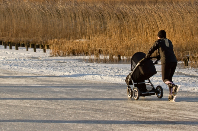 Woman skates on a canal in Fryslân with a baby buggy. Photo by Micha Klootwijk/Shutterstock.