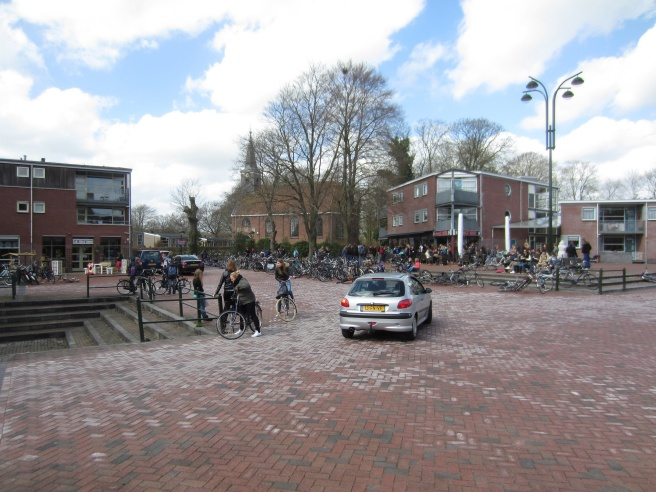 Kids on bikes and a car mix comfortably in this Shared Space in Fryslân. Photo by Mobycon.