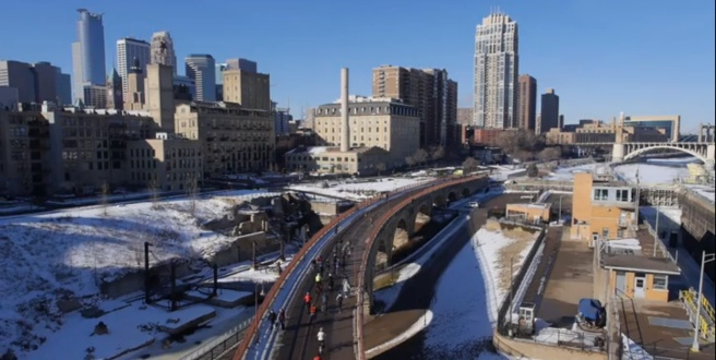 Cycling across the Stone Arch Bridge in Minneapolis, which together with twin city Saint Paul will host the 2016 Winter Cycling Congress. Photo by Maverick Drone Systems.
